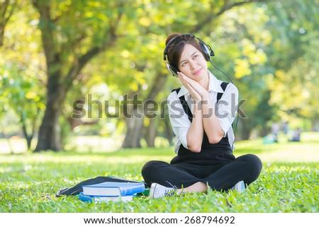 Beautiful Asian Young Woman with Headphones Outdoors. Enjoying Music - stock photo