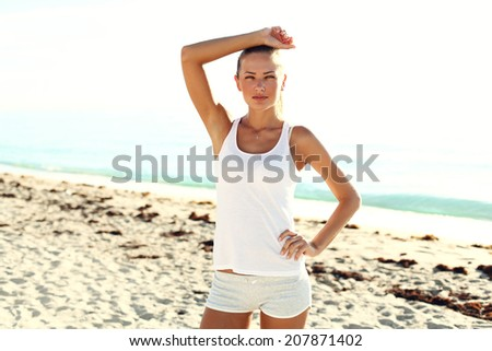 beautiful athlete girl on the beach after workout. - stock photo