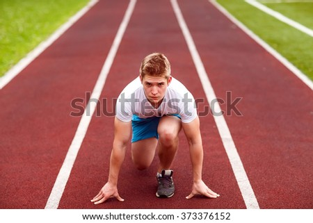 Beautiful athlete on a race track is ready to run