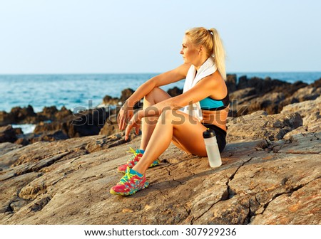 Beautiful athlete woman sitting after sport exercising on the rocks by the sea - stock photo