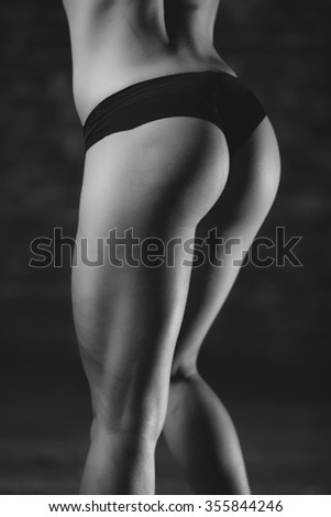 Beautiful athletic ass close-up. Perfect woman sexy buttocks in lingerie. Clean healthy skin. Part of body. Healthy lifestyle, diet and fitness. Black and white photo - stock photo