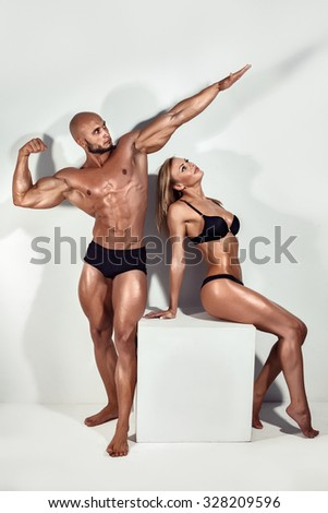 Beautiful athletic couple posing in studio. Bodybuilders - stock photo