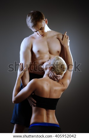 Beautiful athletic couple posing together with passion over black background. Gymnastics, fitness, bodybuilding.  - stock photo