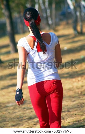 Beautiful athletic girl from behind. Beautiful athletic girl has walking trails in the park. From behind. - stock photo