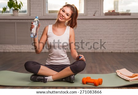 Beautiful athletic girl holding a bottle of water, sitting on the mat. - stock photo