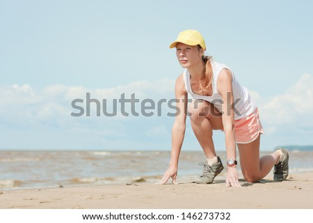 Beautiful athletic girl in a starting position on the beach. - stock photo