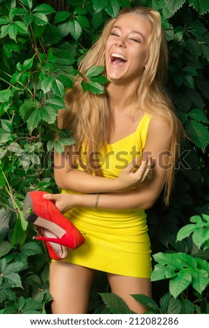 beautiful athletic girl in a yellow dress with red shoes in hand is posing on a background of leaves in the park