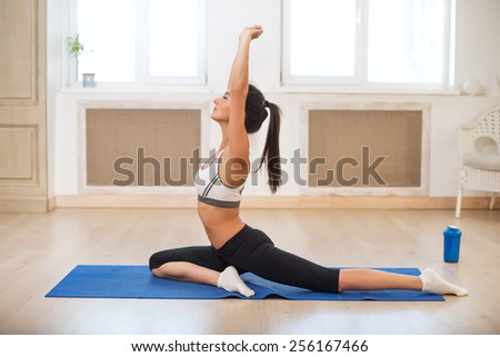 Beautiful athletic sporty woman in the gym doing exercises on the blue mat raising her hands - stock photo