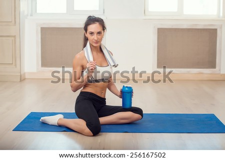 Beautiful athletic sporty woman sitting on yoga mat after some exercises with blue shaker in her hand  and white towel - stock photo