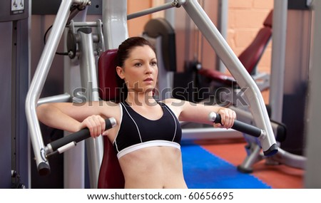Beautiful athletic woman using a bench press in a fitness center - stock photo