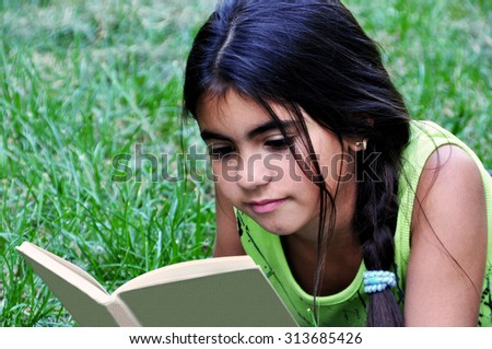 Beautiful attentive  girl lies on green grass and reads book