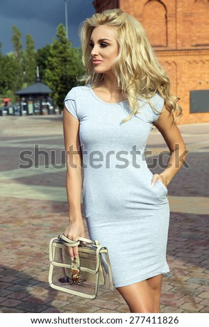 Beautiful attractive blonde woman posing in fashionable dress, looking at camera. - stock photo