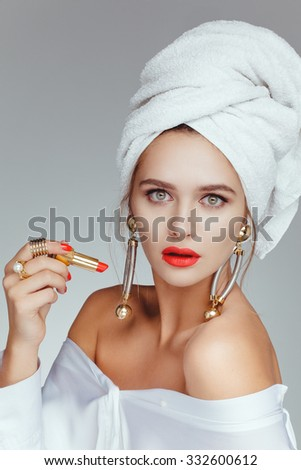 Beautiful attractive charming girl with white towel on her head, big earrings, red lips, taking red lipstick. With red manicure closeup. - stock photo