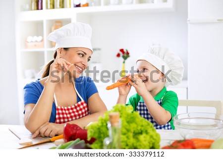 Beautiful attractive mother and child playing with vegetables at home
