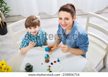 Beautiful attractive mother teach son how to paint easter eggs - stock photo