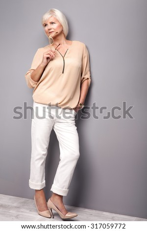 Beautiful attractive senior woman posing in studio, holding eyeglasses in hand. - stock photo