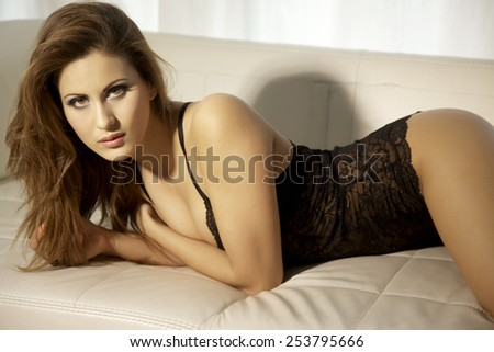 Beautiful attractive sensuality and sexy young adult pretty brunette woman wearing black erotic lingerie on the couch in luxury style apartment  - stock photo