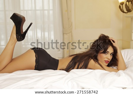 Beautiful attractive sensuality and sexy young adult pretty brunette woman wearing black lingerie panties on the bed in bedroom luxury style elegance hotel apartment - stock photo