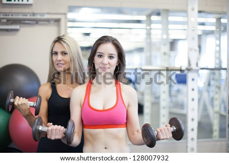 Beautiful attractive woman being trained at a gym