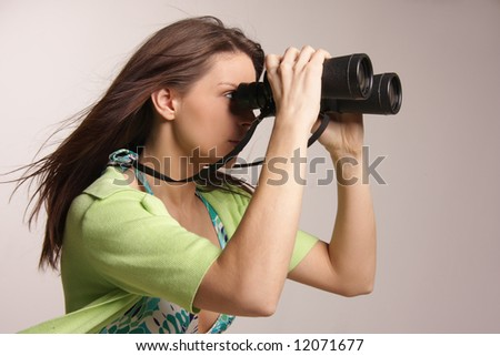 Beautiful, attractive woman looking through binoculars - stock photo