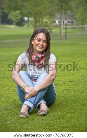 Beautiful attractive woman sitting on a green grass golf course. Smiles. - stock photo