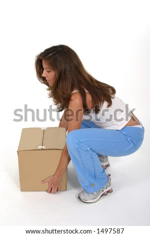 Beautiful attractive woman squatting and lifting a small plain brown box with her knees bent. - stock photo