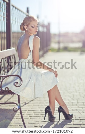 beautiful attractive woman wearing short n and high heels standing in the street in urban model scene. Fashion in a short dress with long sexy legs on the street. Woman sitting on a bench in the city - stock photo