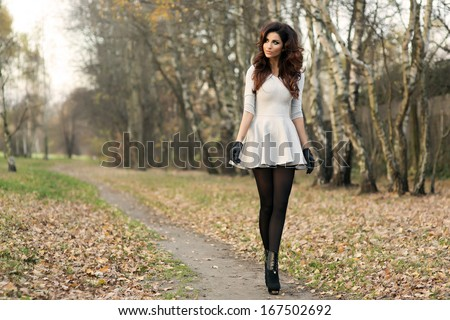 Beautiful attractive young brunette woman in fashionable dress walking in park. - stock photo
