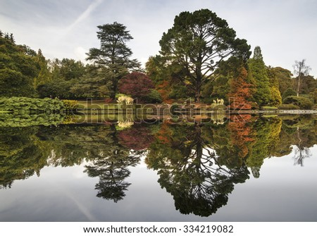 Beautiful Autumn forest landscape reflected in calm lake - stock photo