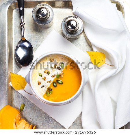Beautiful autumn Pumpkin soup with cream in a white bowl with silverware - stock photo
