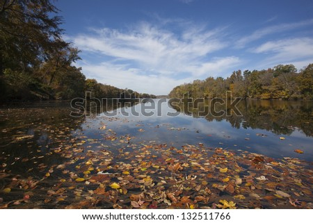 Beautiful autumn river scene showing leaf covered water and spectacular sky - stock photo