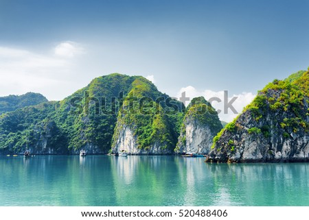 Beautiful azure water of lagoon in the Halong Bay (Descending Dragon Bay) at the Gulf of Tonkin, the South China Sea, Vietnam. Scenic landscape formed by karst towers-isles on blue sky background.