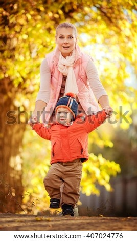Beautiful baby boy and mother in autumn garden - stock photo