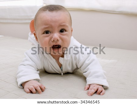 Beautiful baby boy crying on bed. - stock photo