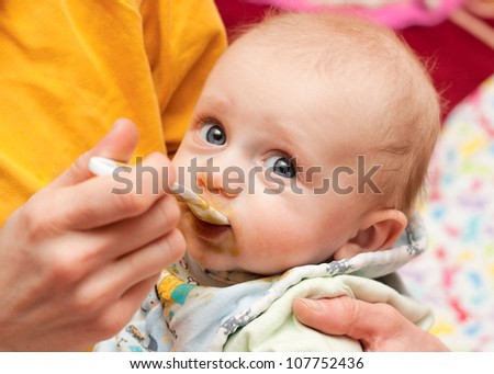 beautiful baby boy eating from a spoon