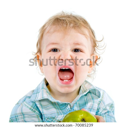 Beautiful baby boy eats green apple.