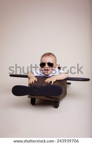 Beautiful baby boy inside a wooden airplane wearing sunglasses - stock photo