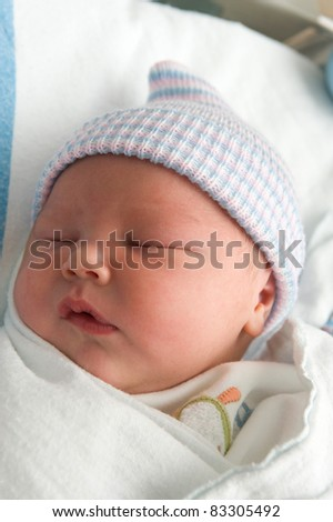 Beautiful baby boy sleeping in the hospital bassinet