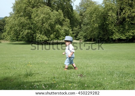 Beautiful baby boy walking alone  in the park.