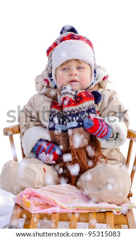 Beautiful baby boy wear in colorful cap scarf sledge in winter, visible snowflakes - stock photo