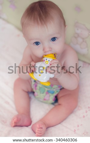 Beautiful baby boy with big blue eyes sitting and sucking on his toy - stock photo