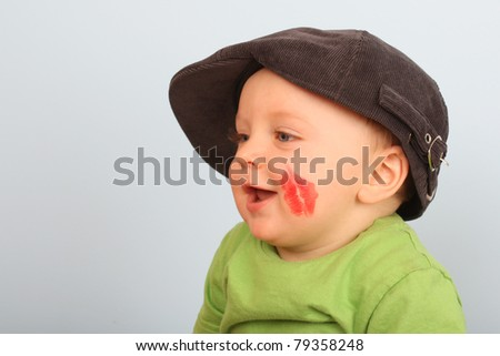 Beautiful baby boy with red lips on his cheek - stock photo