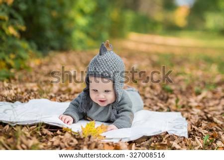 Beautiful baby crawling  in fallen leaves - autumn scene - stock photo