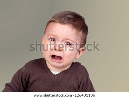 Beautiful baby crying isolated on grey background