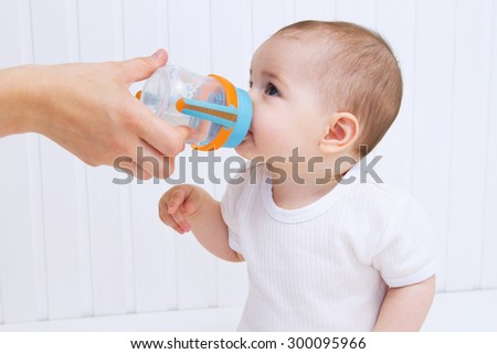 Beautiful baby drinking water from bottle - stock photo