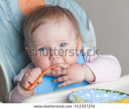 Beautiful baby girl eating mashed. Child eat  itself with a spoon