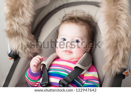 Beautiful baby girl in a pink knitted dress sitting in a stroller - stock photo