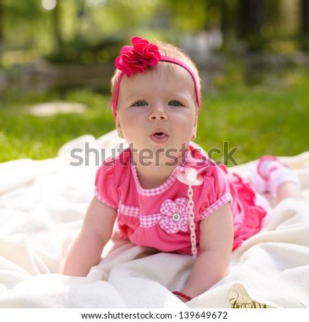 Beautiful baby girl in park, lying down - stock photo