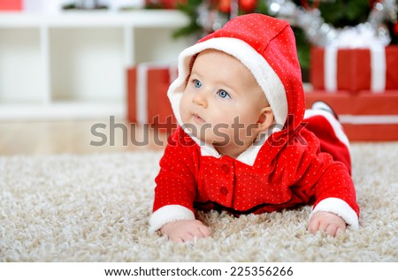 Beautiful baby girl in Santa costume - stock photo