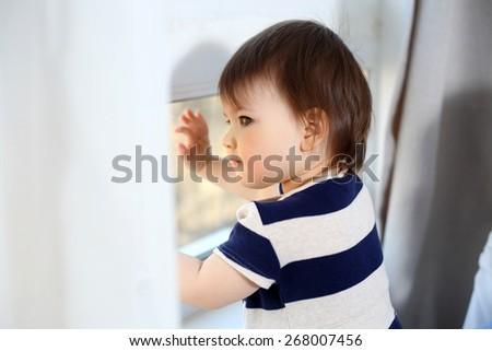 Beautiful baby girl is looking through the window - stock photo